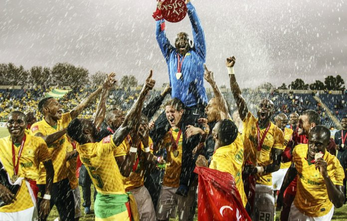 Mamelodi Sundowns coach Pitso Mosimane and the players celebrate winning the league in 2014.