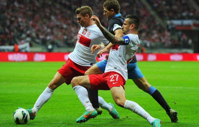 Lukasz Piszczek and Marcin Wasilewsk of Poland challenge Steven Gerrard of England during the Fifa 2014 World Cup qualifier between Poland and England.