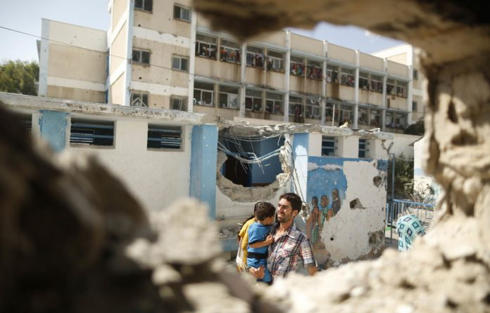 A Palestinian man pictured through a damaged classroom carries a boy as he walks at a United Nations-run school sheltering Palestinians displaced by an Israeli ground offensive.
