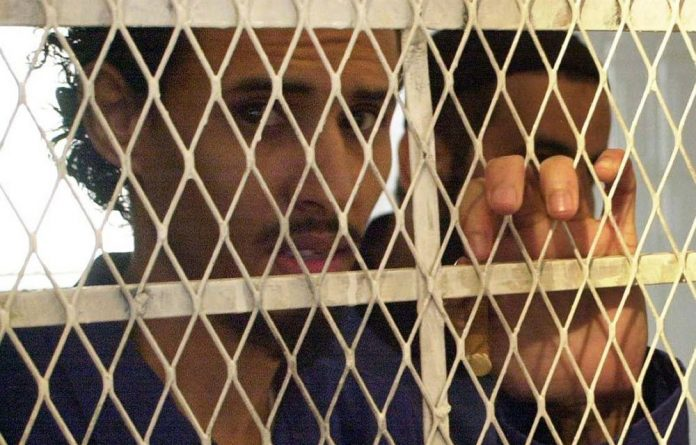 Yemeni al-Qaeda leader Fahd al-Quso standing behind the bars at a court in Sanaa during the trial for six militants charged over the USS Cole bombing in Yemen's Aden port.