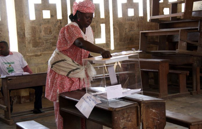 A woman casts her ballot in a polling station for the parliamentary elections in Brazzaville.