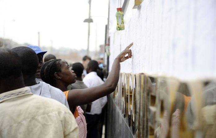 An Angolan woman looks for her name on a list before voting  at a polling station in the outskirts of Luanda.
