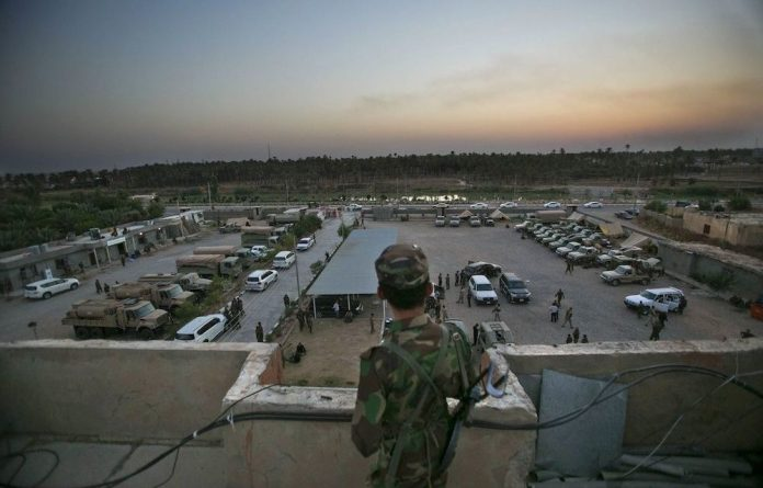 Motivated: A member of the Iraqi Kurdish forces overlooks a military operating base in Iraq's Diyala province while waiting to deploy into Jalawla to fight Isis militants.