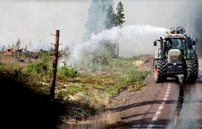 A tractor helps with extinguishing work in the fire-borne area around Farila