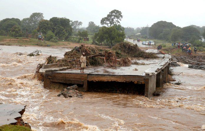 A man looks at a washed away bridge along Umvumvu river following Cyclone Idai in Chimanimani