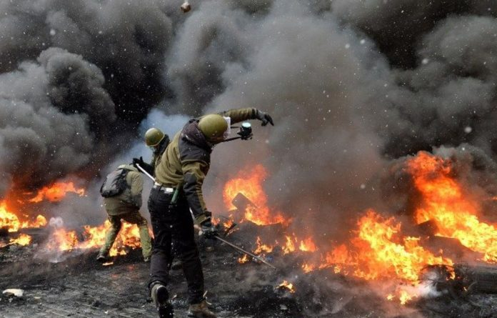 Protestors throw stones as they clash with police in the centre of Kiev on January 22 2014.