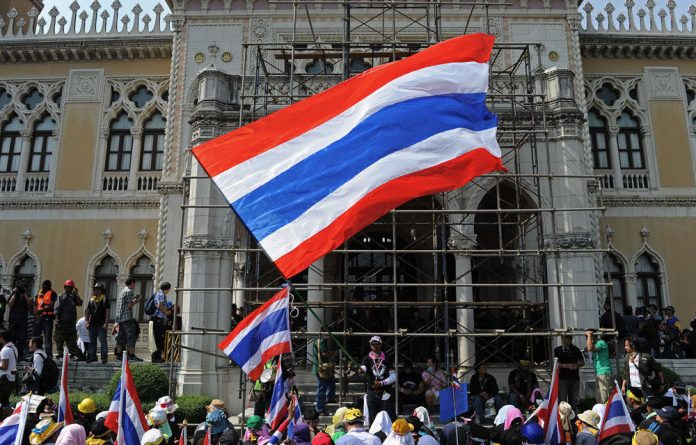 Thai anti-government protesters wave national flags after entering the Government House compound in Bangkok.