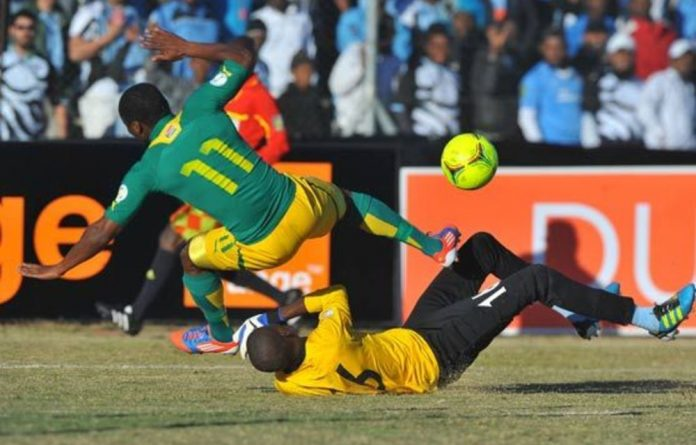Tokelo Ranrie of Bafana thwarted by Kabelo Dambe of Botswana during the FIFA World Cup Qualifier match between Botswana and South Africa.