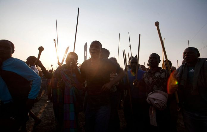 An attempt by the police to disperse striking workers at Marikana's troubled Lonmin mine has ended in a shootout between the two groups.
