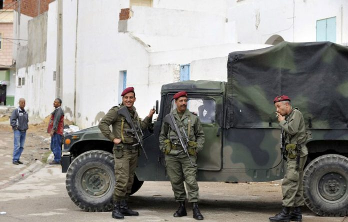 Tunisian soldiers stand guard outside the Douar Hicher mosque in the neighbourhood of Manouba in Tunis on October 31 2012