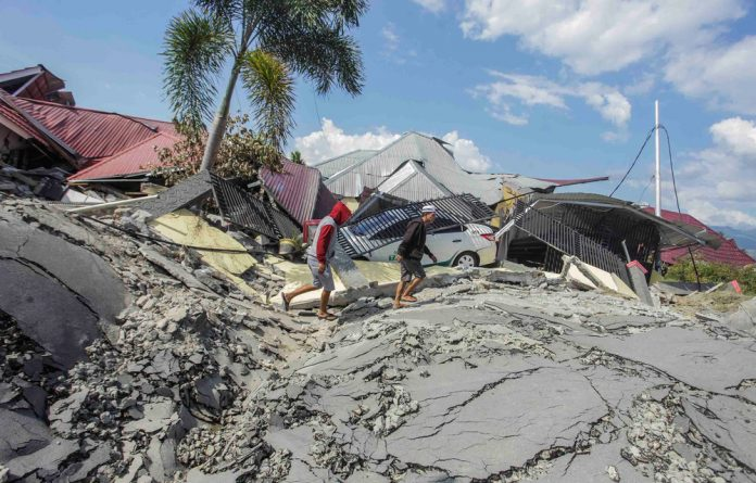 Men walk on damaged road at Petobo sub-district following an earthquake in Palu.