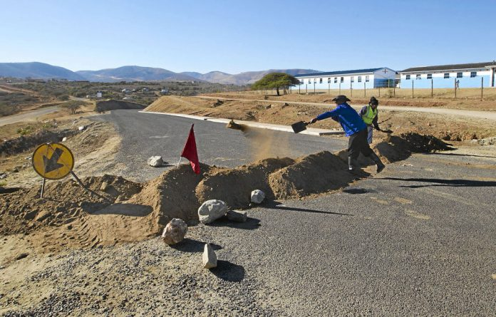 Workers clear sand on a newly tarred stretch of road near President Jacob Zuma's home in Nkandla.