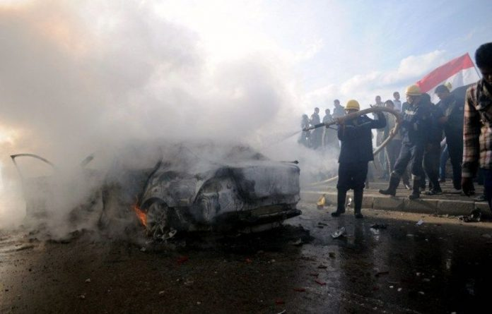Egyptian firefighters douse a burning car set on fire during a demonstration calling for a 'no' vote in a referendum on a new constitution in Alexandria.