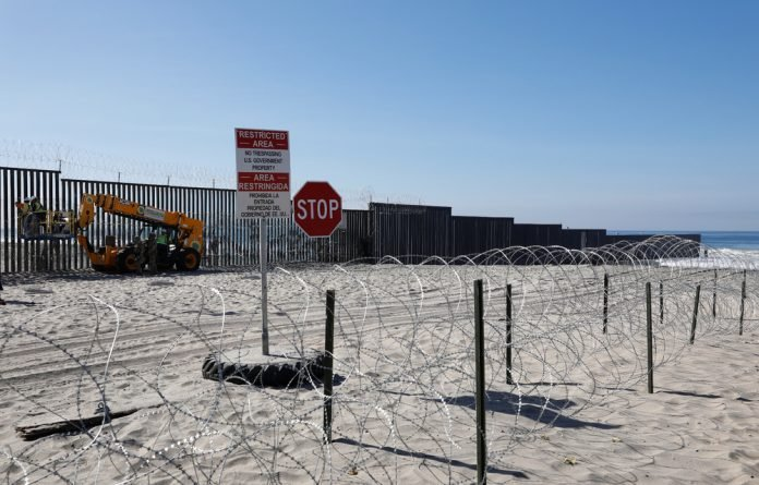 Workers on the U.S. side install concertina wire along the border fence between Mexico and the United States at Border State Park in San Diego