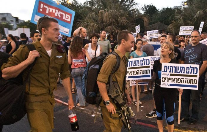 Israeli reservist soldiers and parents whose children were killed during army service hold a mass demonstration in support of a new law to mandate universal conscription to the military.