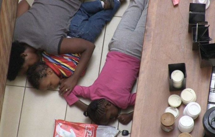 An image grab taken from AFP TV shows two children and a woman taking cover behind a bar inside the Westgate shopping mall.