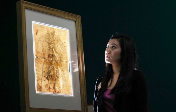An employee of the Queen's Gallery with a 1509 drawing of the cardiovascular system and principal organs of a woman by Leonardo da Vinci.