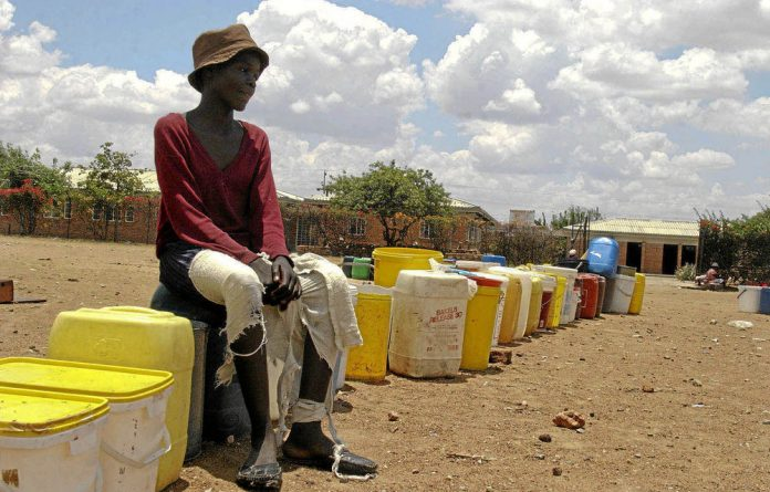 Troubled: Nomusa Mpofu waits to collect water in Magwegwe township in Bulawayo.