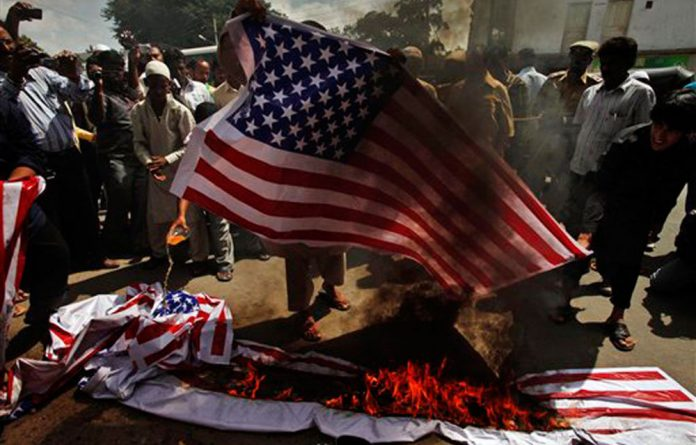Indian Muslims burn a representation of an American flag during a protest in Hyderabad