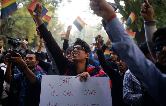 Gay rights activists wave flags and shout slogans as they attend a protest against a verdict by the Supreme Court in New Delhi on December 11.