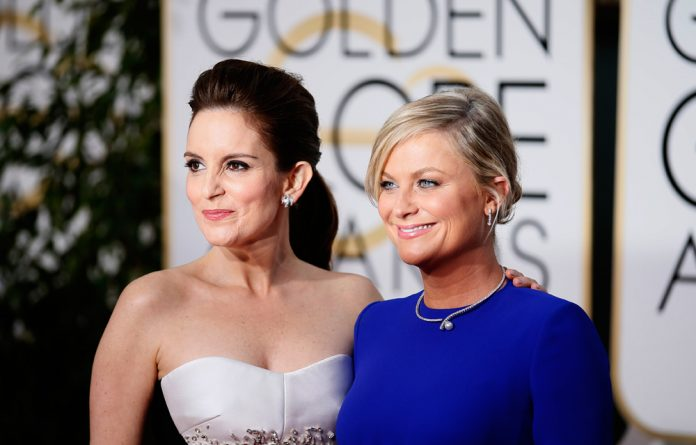 Show hosts Tina Fey and Amy Poehler arrive at the 72nd Golden Globe Awards in Beverly Hills
