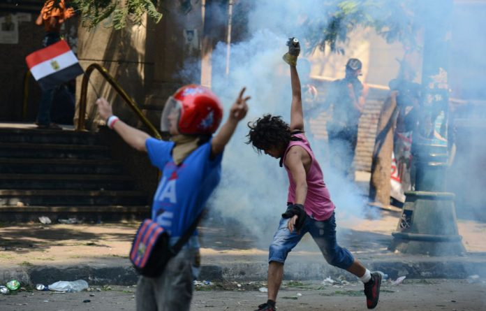 An Egyptian protester throws back a tear gas canister towards the riot police during clashes near the US embassy in Cairo.