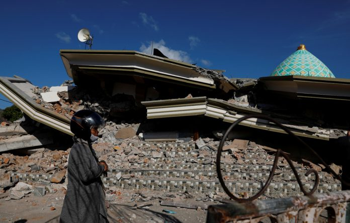 A woman walks near the collapsed ruins of a mosque after an earthquake hit on Lombok island.