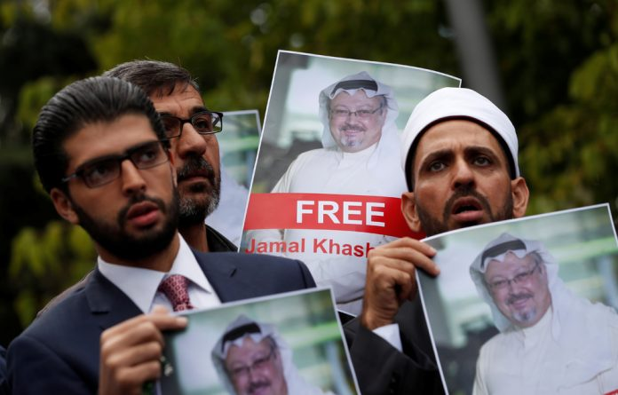 Human rights activists and friends of Saudi journalist Jamal Khashoggi hold his pictures during a protest outside the Saudi Consulate in Istanbul