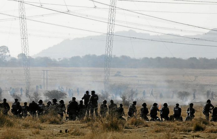 Panic and confusion: Police officers firing at striking miners outside Lonmin's Marikana platinum mine left many wounded and dead in their wake.