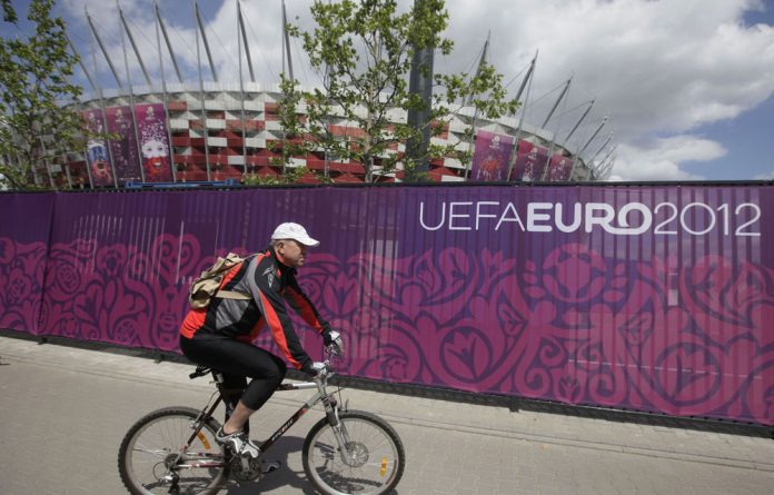 A cyclist passes the decorated fence surrounding Poland's National Stadium in Warsaw