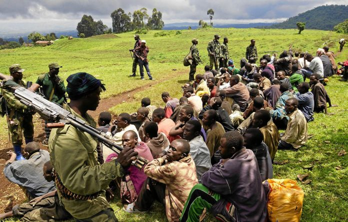 Congolese soldiers guard ­suspected M23 rebels who ­surrendered in Chanzo ­village near Goma.