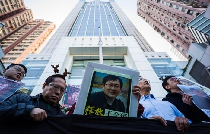 Veteran pro-democracy lawmaker Albert Ho reacts as fellow activists hold placards of detained human rights lawyer Wang Quanzhang at a rally outside the Chinese Liaison Office in Hong Kong on December 26.