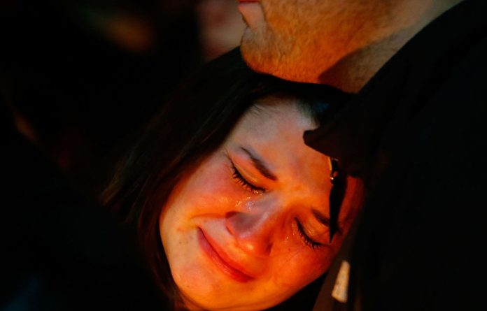 A woman weeps at a vigil to remember the victims of the Sandu Hook school shooting