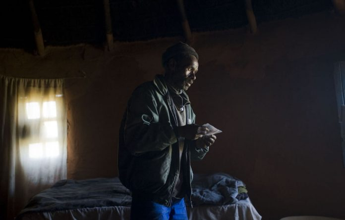Former miner Vuyisile Gibson stands in his mud hut near the town of Tsolo. Gibson underwent medical tests to see whether his poor health is due to decades of breathing dust while working in Anglo American gold mines.