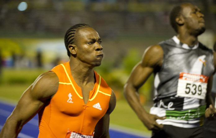 Jamaican sprinter Yohan Blake runs for the victory next to Usain Bolt in the 100m men's final of the Jamaican Olympic Athletic Trials at the National Stadium in Kingston.