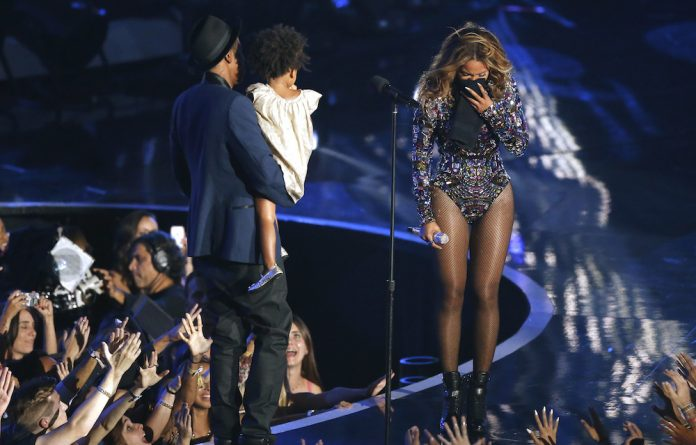 Beyonce reacts as Jay-Z carries their daughter Blue Ivy onstage to present the Video Vanguard Award during the 2014 MTV Video Music Awards.