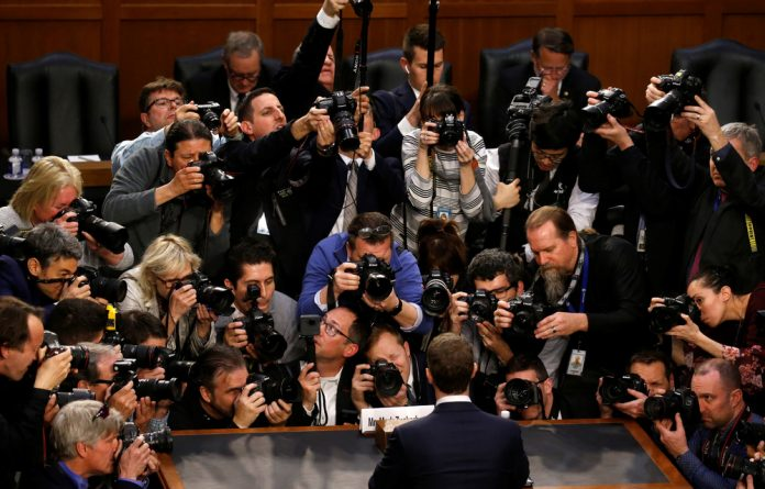 Facebook CEO Mark Zuckerberg is surrounded by members of the media as he arrives to testify before a Senate Judiciary and Commerce Committees joint hearing regarding the company's use and protection of user data.