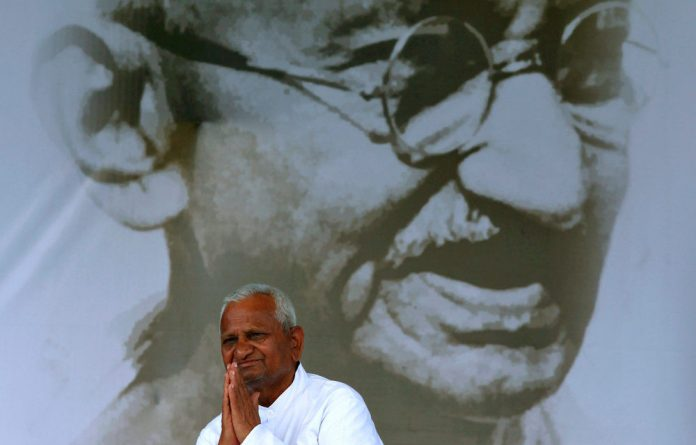 Veteran Indian social activist Anna Hazare greets a supporter as he sits in front of a portrait of Mahatma Gandhi
