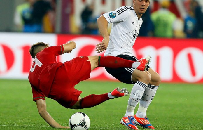 Germany's Lukas Podolski and Portugal's Miguel Veloso tussle during a Euro 2012 match in Lviv