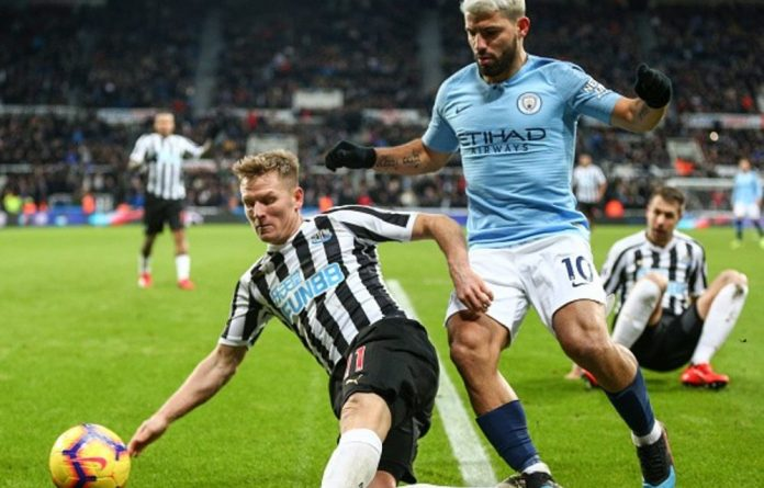 Matt Ritchie of Newcastle United stops the ball from going out of play after Sergio Aguero of Manchester City was tackled