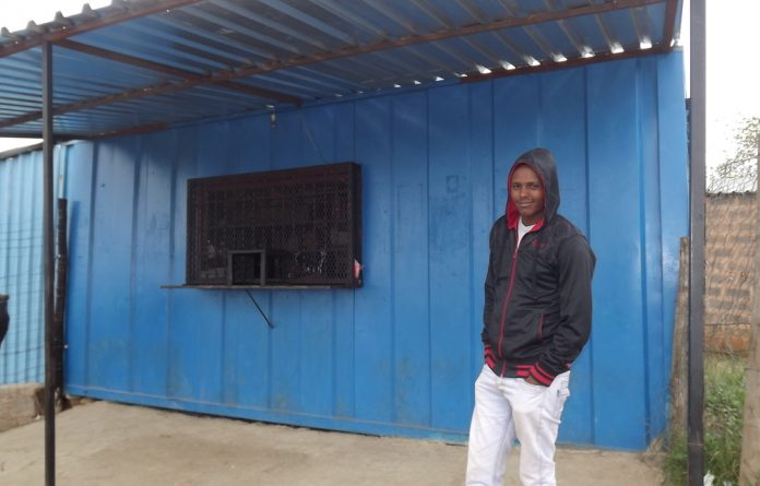 Mangistu Alamrl standing in front of one of his containers. His shop was looted and goods taken.