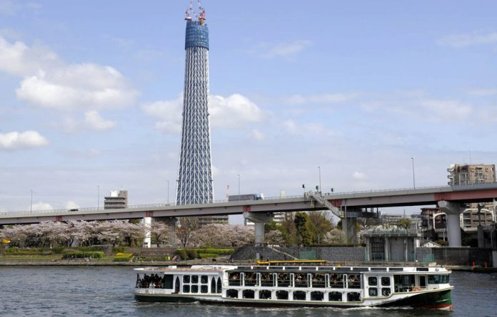 A Tokyo Cruise boat goes down the Sumida river as it passes the Tokyo Sky Tree in the Japanese capital.