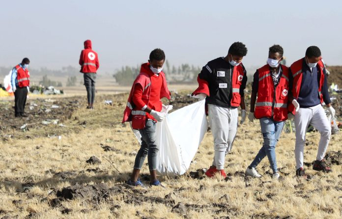 Members of the search and rescue team carry dismembered parts of passengers bodies at the scene of the Ethiopian Airlines Flight ET 302 plane crash