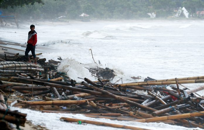 A resident affected by the tsunami stands next to debris in Carita beach in Pandeglang