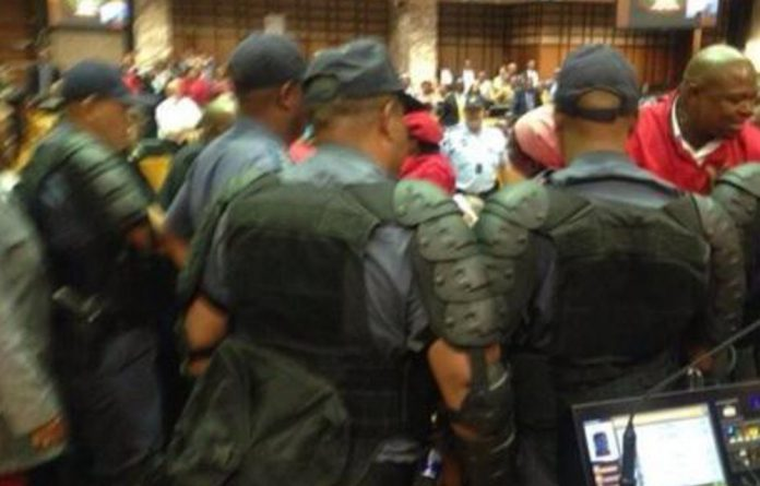 Police remove an EFF MP from the National Assembly.