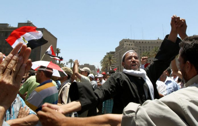 Egyptian supporters of the Muslim Brotherhood dance during a demonstration in Cairo's Tahrir square.