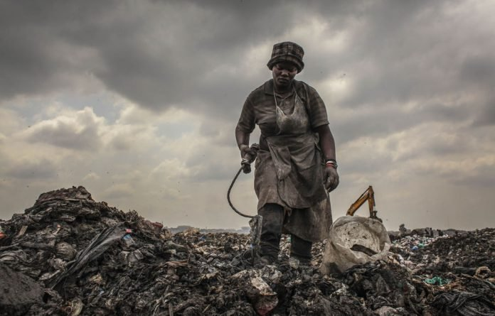 A women scours Nairobi's Dandora dump for recyclable waste.