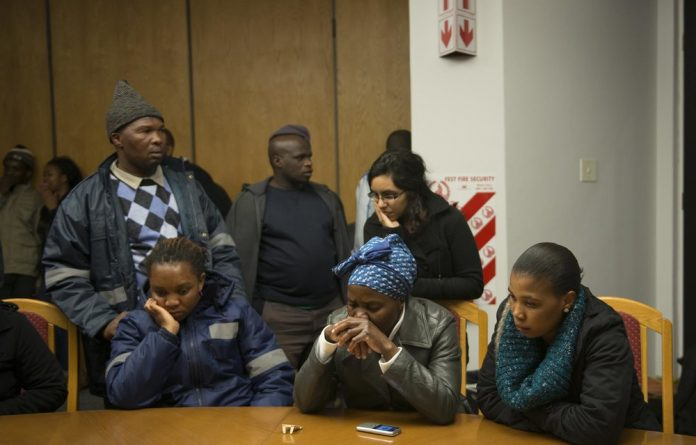Families of the slain Marikana miners gather in a Lonmin boardroom to listen to Zuma's report on national television on June 25
