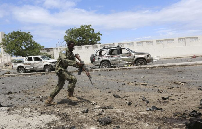 A Somali government soldier runs to take position in front of the Parliament during a clash with al-Shabab.