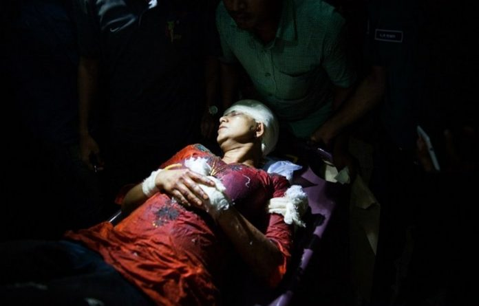 Avijit Roy's wife Rafida Ahmed Banna is carried on a stretcher after she was seriously injured by unidentified assailants during an attack on her husband.